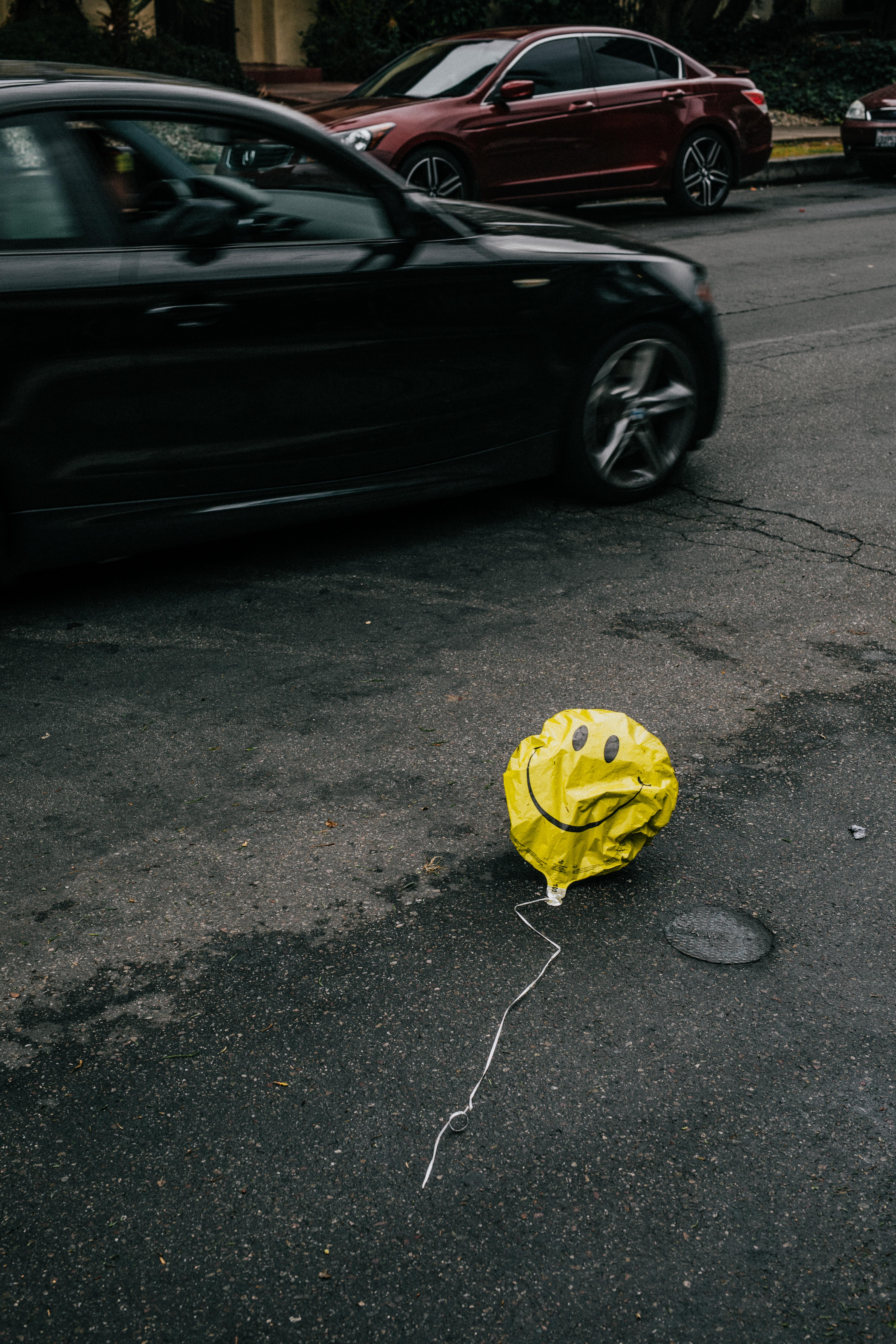 globus desinflat amb careta somrient al mig de la carretera amb cotxes al fons