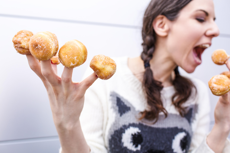 Dona menjant minidonuts que té a cada un dels dits