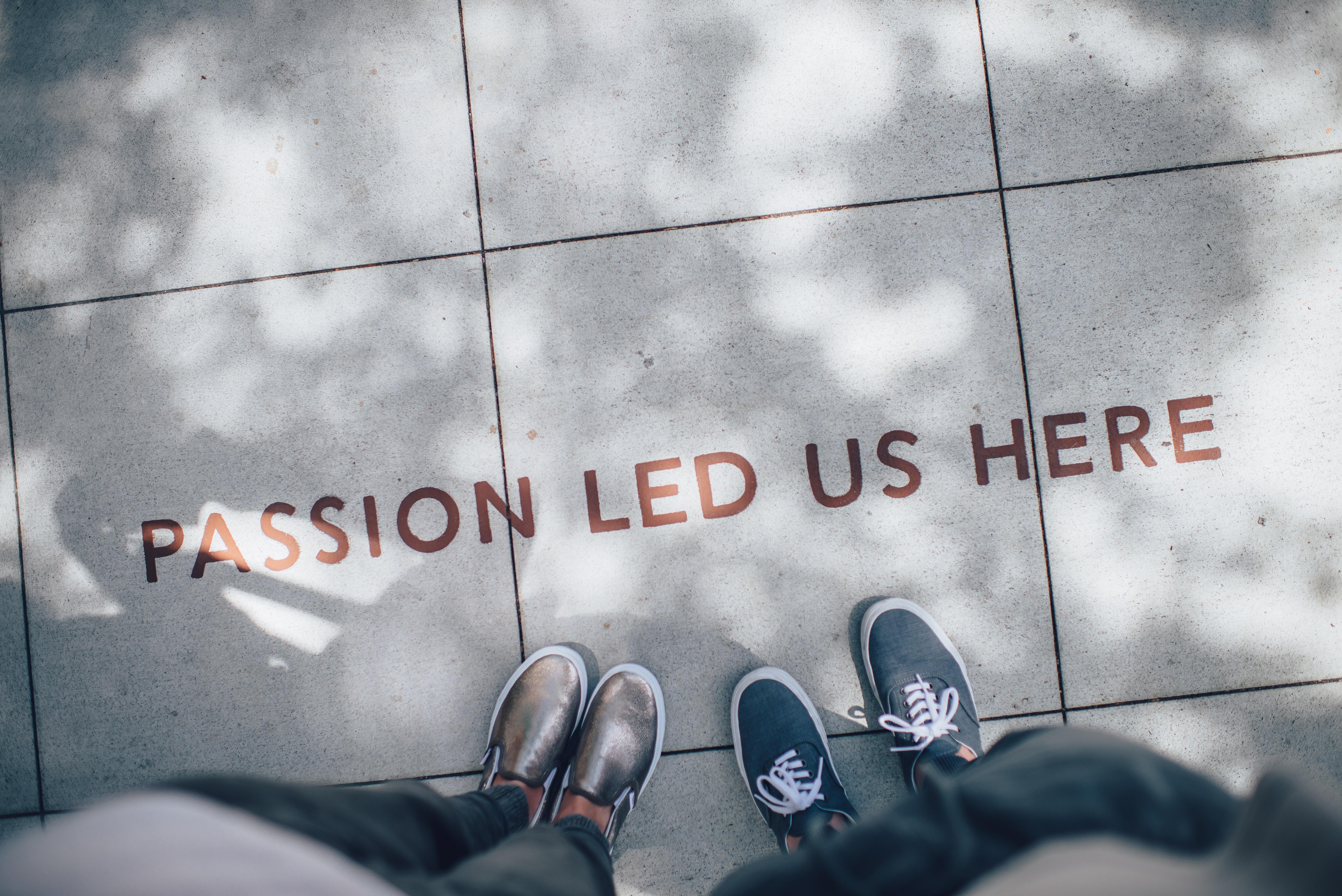 Dos parells de peus parats davant de la frase Passion led us here