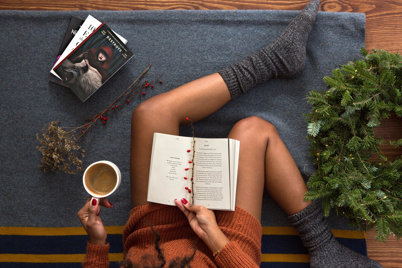 Cames de dona introvertida amb llibres i una tassa de te