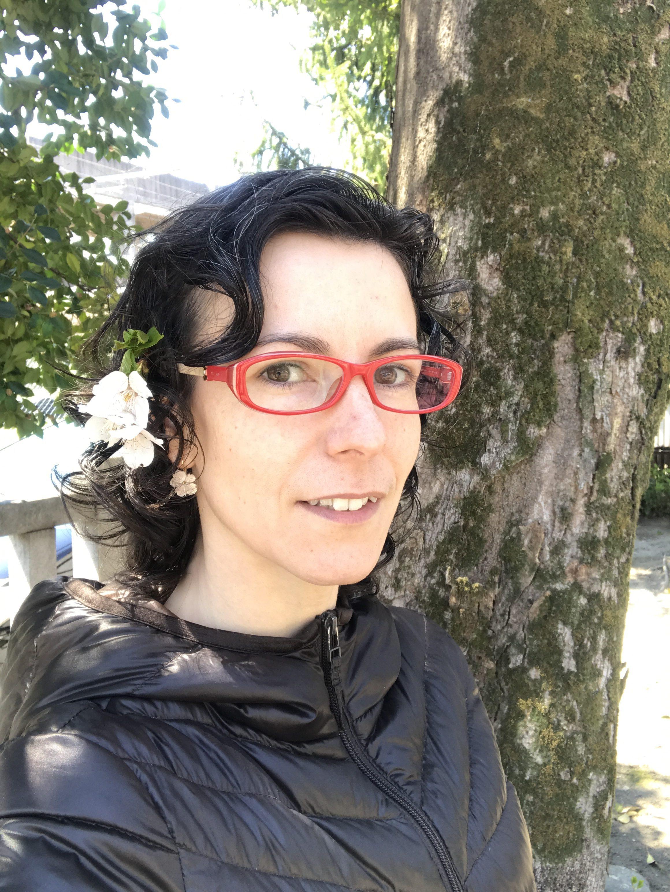 mujer con gafas rojas y flor de cerezo en la oreja